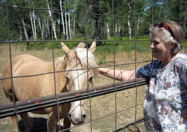 Aunt Dian petting one of the horses at the ranch