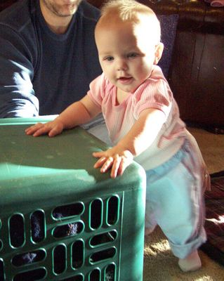 Annabel standing up against a laundry basket (#1 with Daddy's chin)