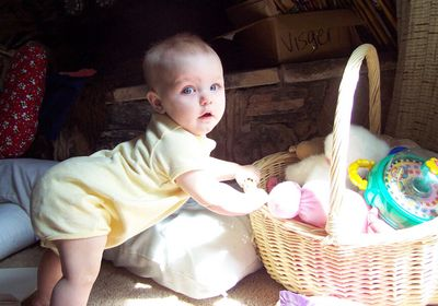 Annabel trying to climb into her toy basket