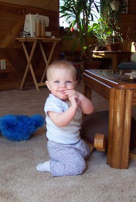 Annabel trying to stand up at the coffee table by herself